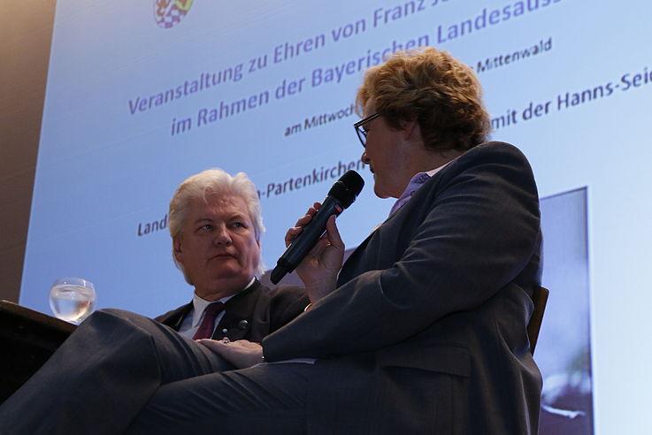 Links sitzend ein Mann, rechts neben ihm eine Frau im Interview