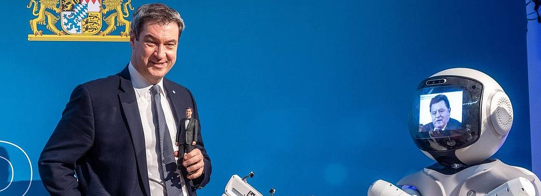 Söder steht neben dem Roboter Garmi, auf dessen Bildschirm Franz Josef Strauß zu sehen ist