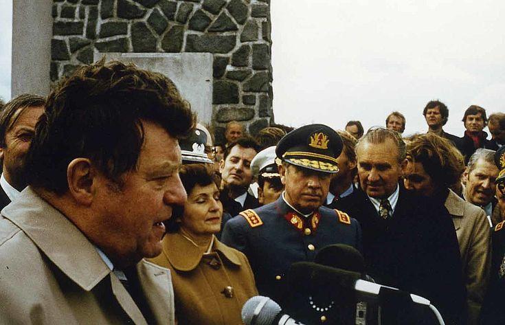 Franz Josef Strauß spricht vor dem Denkmal am Lago Llanquihue zur 125. Jahrfeier der deutschen Einwanderung nach Chile im November 1977, im Hintergrund das Ehepaar Pinochet