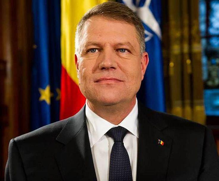 Mann mit zurückgekämmten Haar, in Anzug und Krawatte gekleidet schaut ernst zur Seite. Im Hintergrund sind Flaggen, darunter auch die Europäische zu sehen.