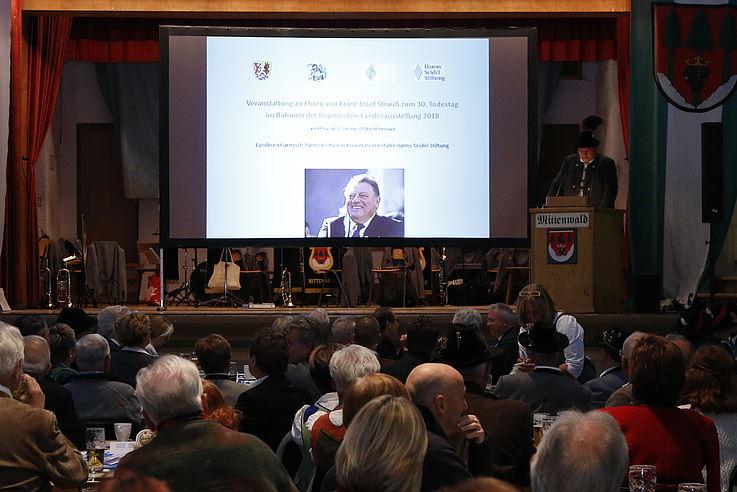 Bühne von vorne mit Redner rechts, im Hintergrund eine Power-Point Folie