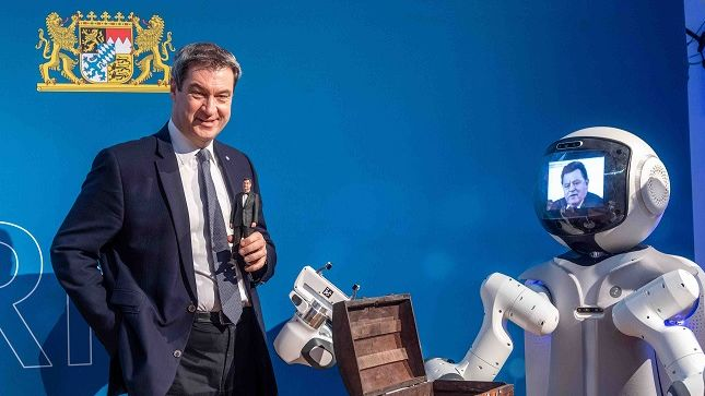 Ministerpräsident Söder steht mit einem kleinen 3-D Söder in der Hand neben dem Roboter Garmi, auf dessen Bildschirm Franz Josef Strauß zu sehen ist