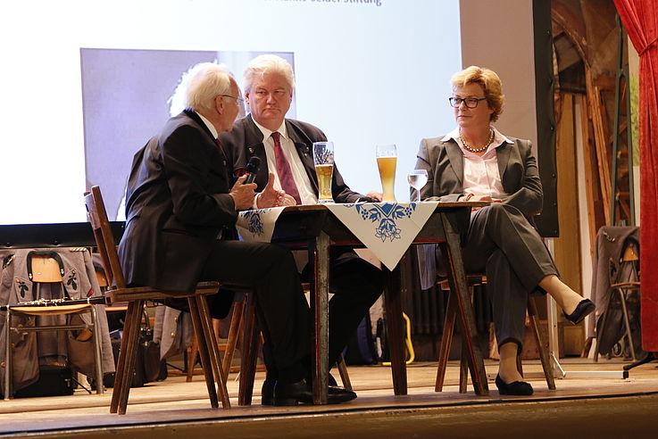 Zwei Männer rechts und eine Frau links, sitzend an einem Tisch auf der Bühne