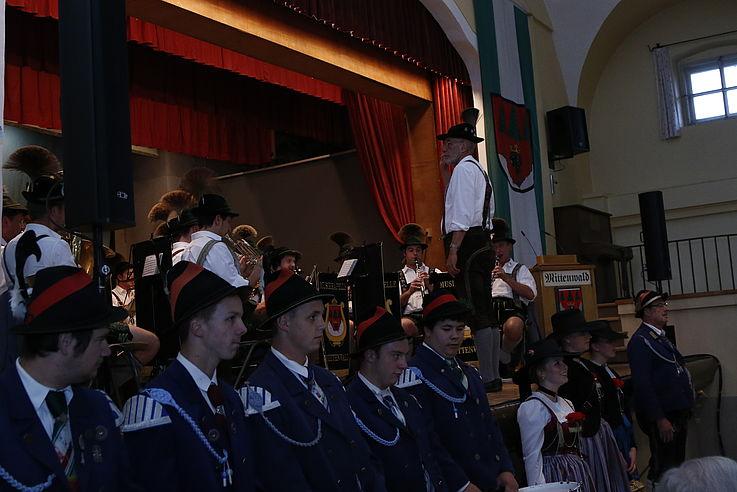 Gruppe von Männern vor einer Bühne, auf der Bühne eine Musikkapelle